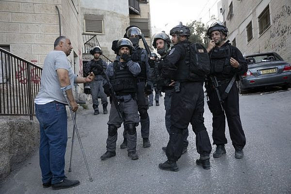 Muhammad Abu Hummus, a political activist from the East Jerusalem neighborhood of Issawiya, is seen speaking to Israeli riot police during a raid on the neighborhood. (Oren Ziv/Activestills.org)