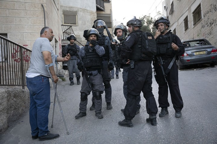 Muhammad Abu Hummus, a political activist from the East Jerusalem neighborhood of Issawiya, is seen speaking to Israeli riot police during a raid on the neighborhood. (Oren Ziv/Activestills.org)