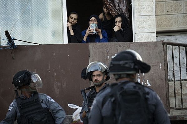 Palestinian women look on during a raid by Israeli police in the East Jerusalem neighborhood of Issawiya, July 1, 2019. (Oren Ziv/Activestills.org)