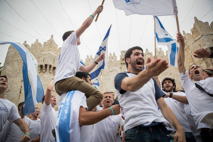 Thousands of Jewish wave the Israeli flags as they celebrate Jerusalem Day in Damascus Gate on their way to the Western Wall. Jerusalem Day celebrations, May 13, 2018. (Yonatan Sindel/Flash90)