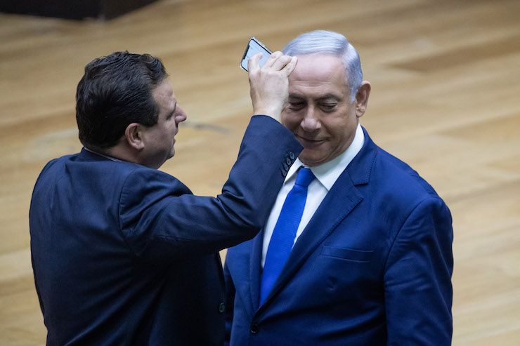 "Joint List party leader Ayman Odeh films Israeli Prime Minister Benjamin Netanyahu during a discussion on the ""camera law"" at the Knesset in Jerusalem on September 11, 2019. (Yonatan Sindel/Flash90)"