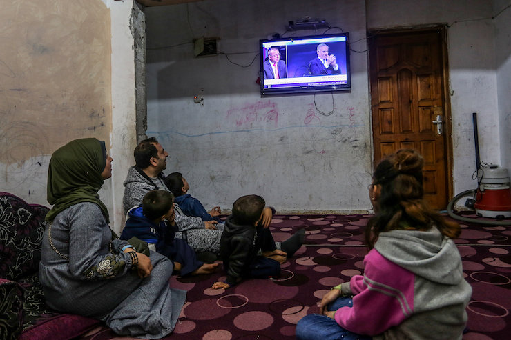 A Palestinian family watch news of Israeli elections at their home in Khan Younis in the southern Gaza Strip, April 10, 2019. (Abed Rahim Khatib/Flash90)