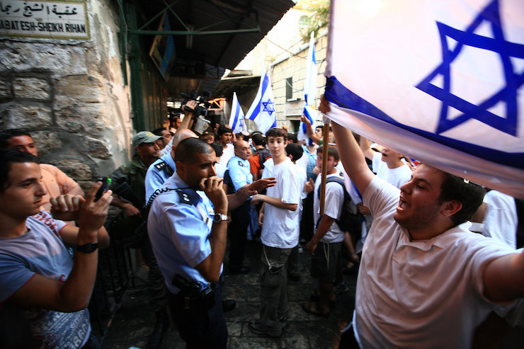 A Jewish Israeli man shouts at Palestinians while waving the Israeli flag in the Muslim Quarter of the Old City of Jerusalem on Jerusalem Day, June 2, 2008. (Nati Shohat/Flash90)