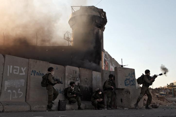 Illustrative photo of Israeli soldiersfiring tear gas at Palestinian protesters at Qalandiya checkpoint. (Nati Shohat/Flash90)