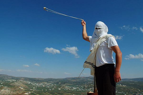 Illustrative photo of a masked Jewish settler with a slingshot in the West Bank settlement of Yitzhar, May 19, 2013. (Mendy Hechtman/Flash90)