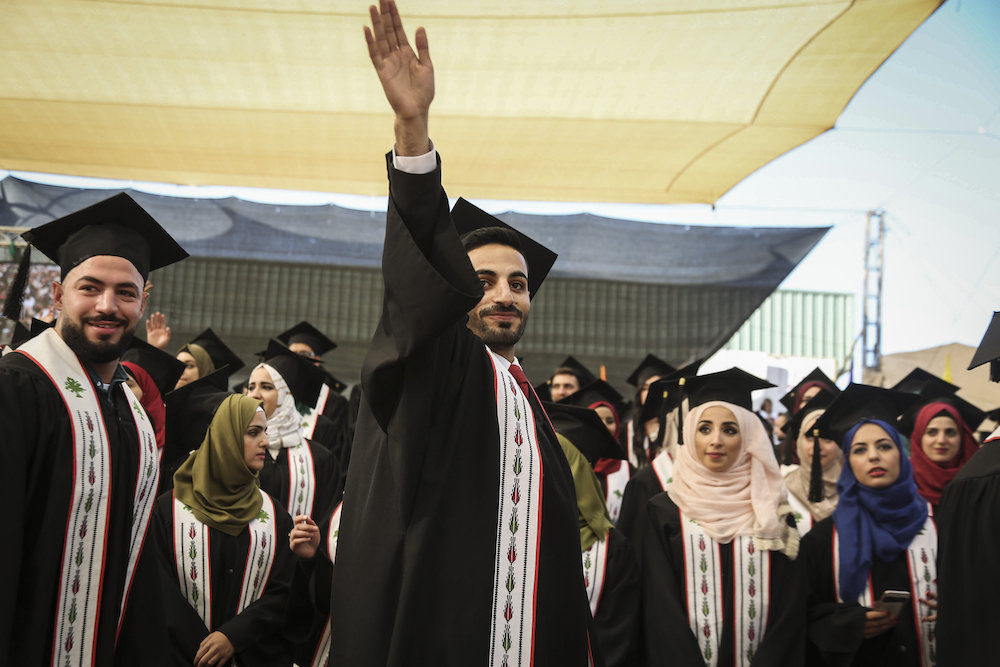 Palestinian students raise their diploma during their graduation ceremony at the end of the academic year on May 20, 2016 at Birzeit University in the West Bank town of Birzeit, near Ramallah. (Flash90)