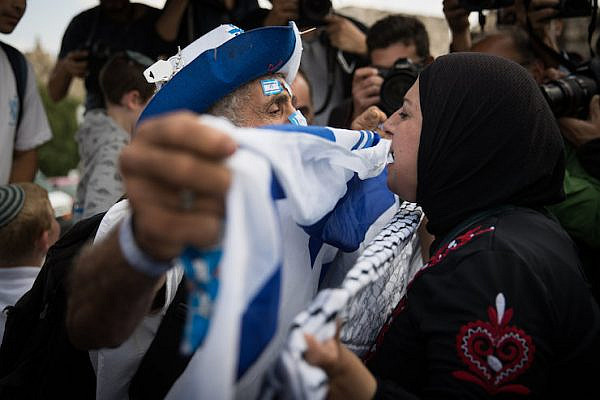 "A Jewish Israeli man holding an Israeli flag confronts a Palestinian woman holding a kaffiyeh on the sidelines of the ultra-nationalist ""Jerusalem Day"" march, May 13, 2018. (Yonatan Sindel/Flash90)"