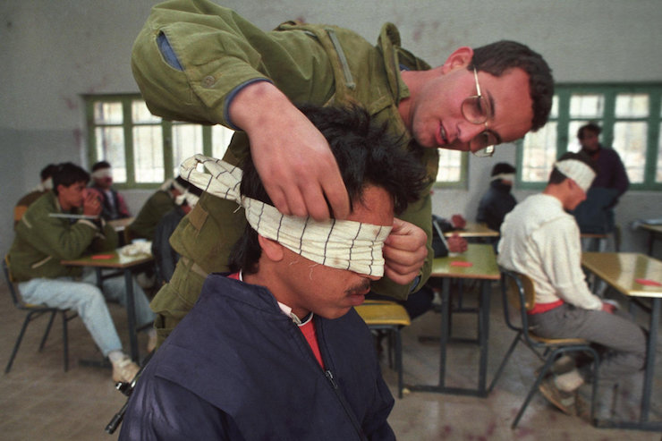 Illustrative photo of an Israeli soldier blindfolding a Palestinian prisoner. (Nati Shohat/Flash90)