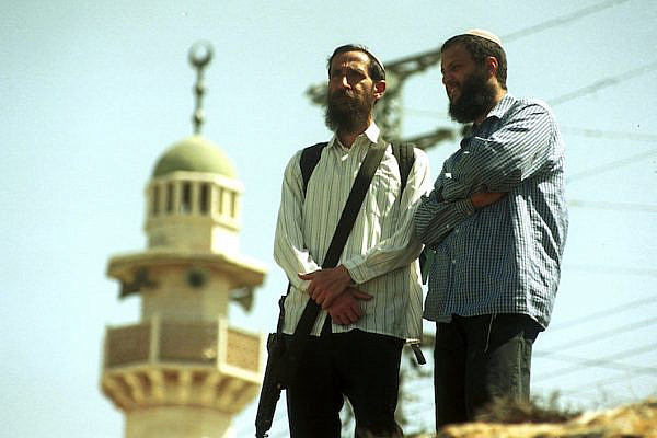 Two settlers, one of them carrying a gun, stand near a mosque in the West Bank city of Hebron, April 1, 2001. (Nati Shohat/Flash90)