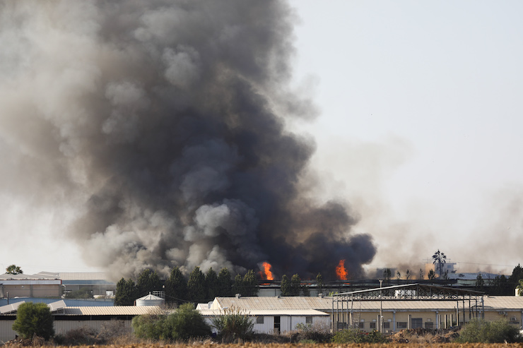 Flames rise fire at a factory in Sderot, caused by rocket fired from the Gaza Strip, November 12, 2019. (Noam Revkin Fenton/Flash90)