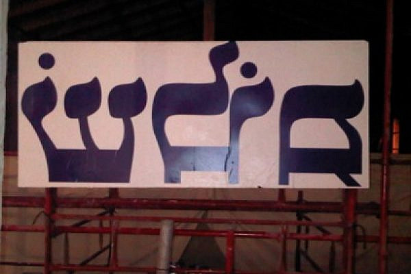 'Shalom' (peace) banner photographed from behind, so that it appears backward. (photo: Issa Boursheh)
