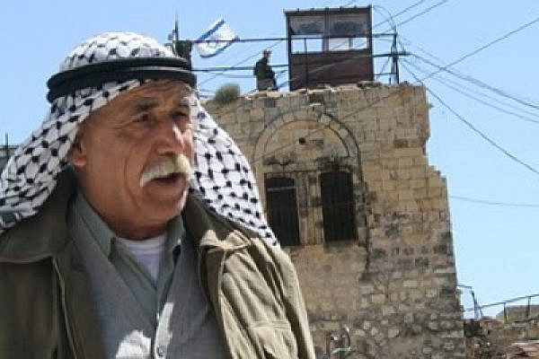 Palestinian in Hebron, with Israeli flag in the background (photo: Avidgor Charlemagne)
