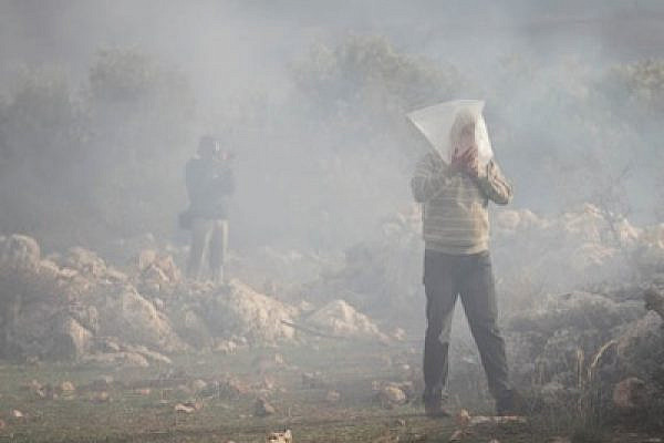 A Palestinian man in Bil'in breathes in a plastic bag while surrounded by tear gas  (photo: Oren Ziv/activestills.org)