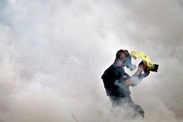 Photojournalist Mati Milstein surrounded by a cloud of tear gas. Bil'in, 31 December 2010 (photo: Fadi Arouri)