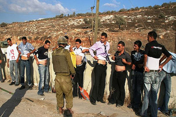 Solider Inspecting Palestinians from Awarta. Photo: michaelramallah/Flickr