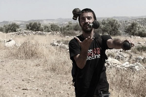 A man juggles with empty tear gas canisters. Bil'in, June 17 2011 (photo: Yossi Gurvitz)