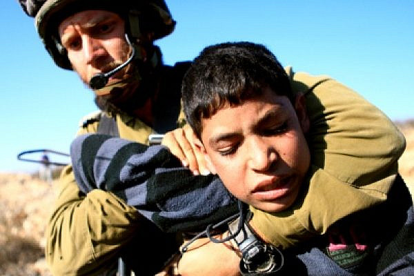 A 14 year-old Palestinian child is arrested by an Israeli soldier during a demonstration in Beit Omar (photo: Anne Paq/Activestills.org)