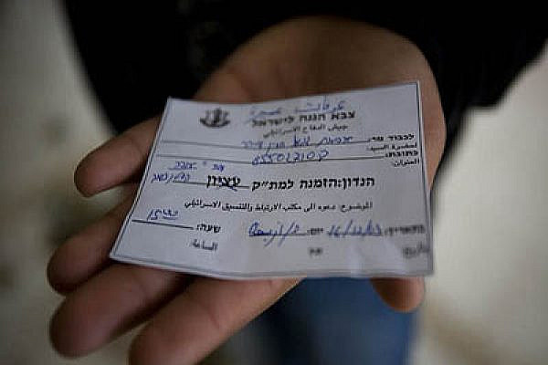 A Palestinian displays an Israeli military court summons. Photo by Activestills.org