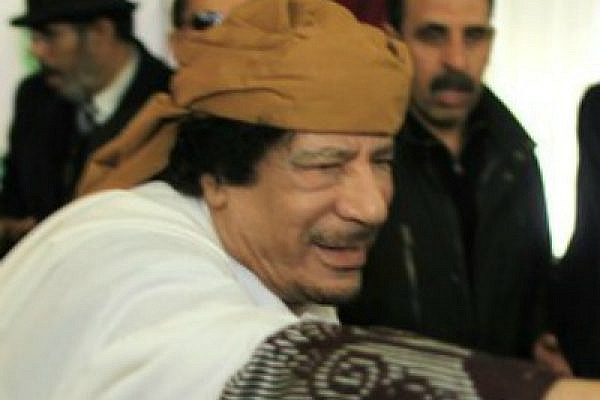 Libyan leader Muammar Gaddafi reaches out before making a speech in Tripoli which he sought to defuse tensions after more than 10 days of anti-government protests in Libya, March 2, 2011. (photo: Ahmed Jadallah/Flickr CC)
