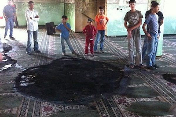 Palestinian children at a burnt mosque (Photo: Aziz Abu Sarah)