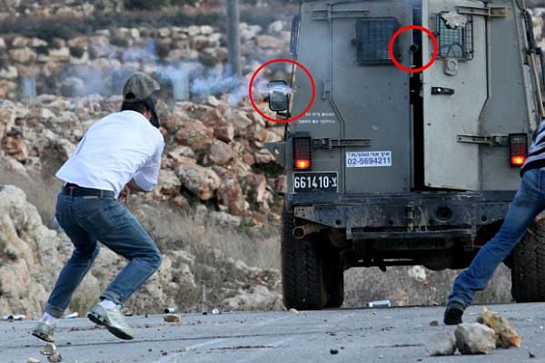 Mustafa Tamimi, a moment before he was injured. The weapon that shot him is circled in red, as is the tear gas canister that caused the fatal injury. Ibrahim Bornat can be seen in the edge of the frame. (photo: Haim Scwarczenberg)