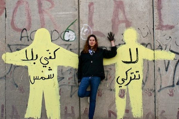 Tamara Masri, the author, against a mural she painted on the separation wall