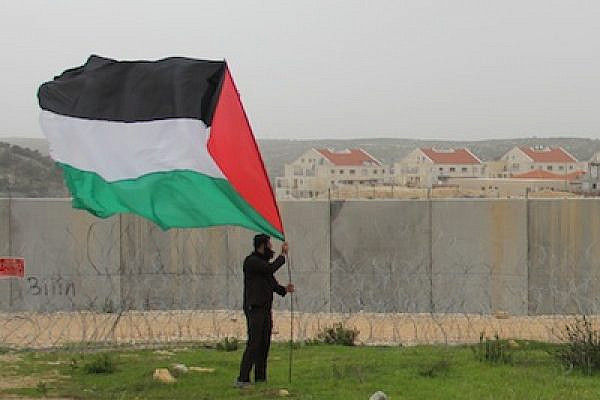 A Palestinian stakes a giant flag in front of the Separation Wall in the village of Bi'lin with a Jewish settlement in the background. (photo: Omar Rahman)