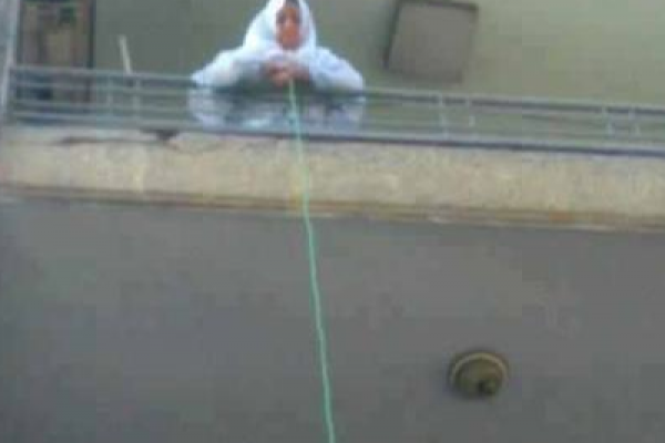 Egyptian Muslim woman lowering water to Christians (Photo: Facebook)