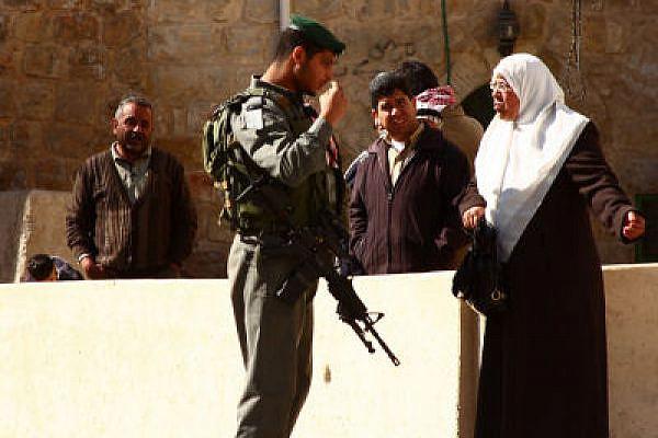 Israeli border policeman faces a Palestinian woman in Hebron (Photo: Yossi Gurvitz)