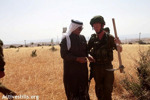 An Israeli soldier holds a Palestinian farmer's tools [illustrative photo] (Anne Paq / Activestills)