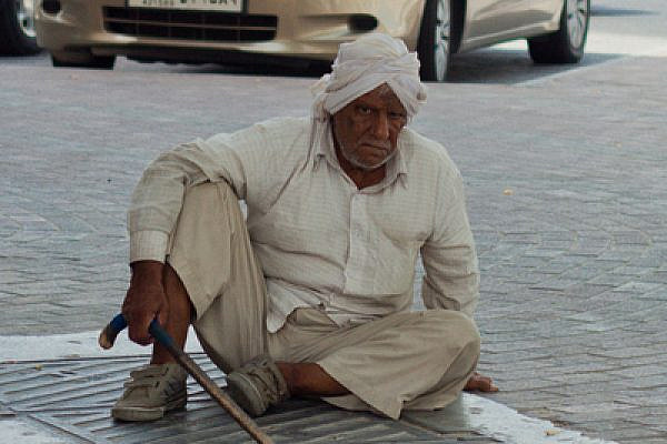 A Pakistani man sits on a street in Doha, Qatar in front of luxury vehicles, July 2011 (photo: PeregrinoWillReigh/fickrcc)