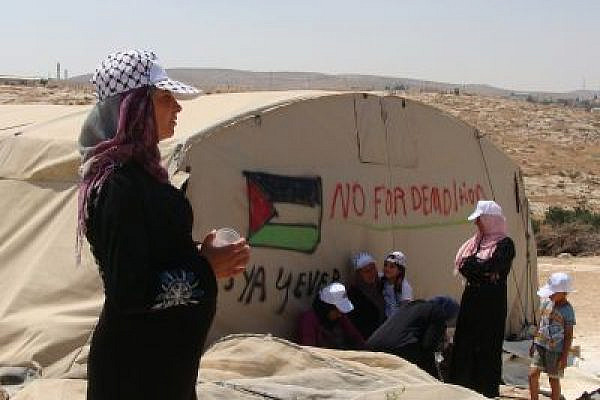 "Palestinian woman in Susya stands next to a tent that reads ""No for demolition"" (photo: Mya Guarnieri)"