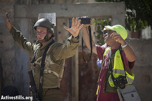 An Israeli soldier prevents a Palestinian cameraman to document the house to house search conducted by the Israeli army in the center of the village during the weekly protest against the occupation and settlements in the West Bank village of Nabi Saleh, August 24, 2012. (photo: Oren Ziv/Activestills.org)