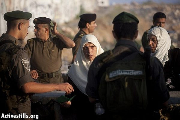 A Palestinian woman shows her ID to an Israeli border policeman, while Palestinian security forces stand in the background, as she crosses from the Qalandiya checkpoint on the first Friday of Ramadan, July 20, 2012. (photo: Oren Ziv/ Activestills.org)