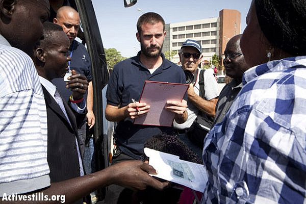 A representative of the Authority of Population and Immigration checks South Sudanese people boarding a bus for Ben-Gurion airport. The refugees were gathered in a raid conducted by Oz Unit. Arad, Israel, June 17, 2012. (Photo: Yotam Ronen/Activestills.org)