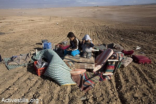 Children sit atop belongings that were recovered from their home, which was demolished by Israeli authorities.