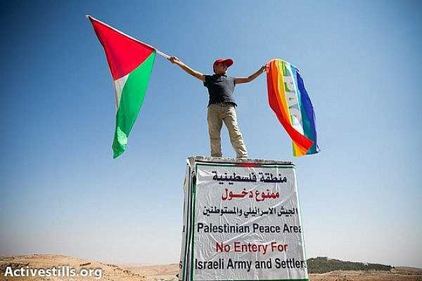 During a solidarity march, a Palestinian boy waves a peace flag and the Palestinian flag while standing atop a concrete slab which usually bears warnings placed by the Israeli military declaring a firing zone, South Hebron Hills, September 22, 2012. (photo: Yotam Ronen/Activestills.org)
