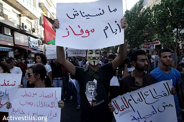 "A mask protester wears a sign reading "" we did not forget the Mofaz daysl "" (referring to earlier protest against a planned visit of Israeli Vice Prime Minister Shaul Mofaz) during a protest marching to the Muquata, the PA headquarters; in the West bank city of Ramallah to protest the rising cost of living, especially fuel and food, and calling for the resignation of the Palestinian National Authority's Salam Fayyad and the end of the Paris protocol, September 11, 2012. Protesters condemned continuous increases in taxes, cuts to public sector wages and the oppressive rule of the Paris Protocol on Economic Relations, an agreement signed with Israel in 1994, which laid out the economic relations between Israel and the PA within the Oslo framework, and which turned out to be mostly about ensuring Israel's economic domination of the Palestinian market and has prevented the development of an independent Palestinian economy. Some protesters also called for the end of the Oslo accords.