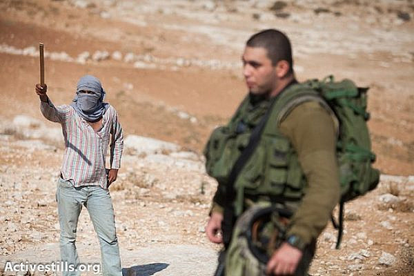 Protected by an Israeli soldier, a masked settler threatens activists with a stick in front of Ma´on settlement during a solidarity march in the South Hebron Hills, September 22, 2012. (photo: Activestills.org)