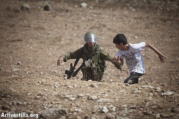 An Israeli soldier tries to arrest a Palestinian boy during the weekly demonstration against the occupation in the village of Nabi Saleh, September 21, 2012. (photo: Oren Ziv/ Activestills.org)