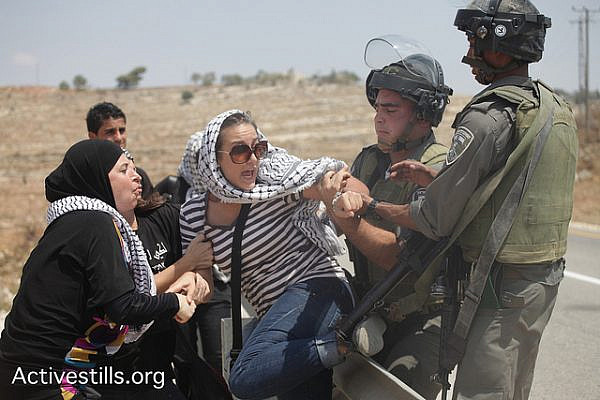 An Israeli solider attempts to arrest an activist during a protest in the West Bank village of Nabi Saleh, August 31, 2012. (photo by: Anne Paq/Activestills.org)