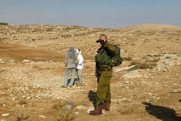 IDF soldier turns a blind eye to violent settlers from Havat Maon (photo: Israeli Ta'ayush activist)