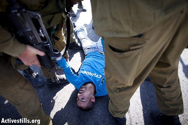 Israeli soldiers arrest Ashraf Abu Rahma from Bilin, as Palestinian and international activists block Road 443, which connects Tel Aviv and Jerusalem through the West Bank, during a protest against the violence of  the Israeli settlers, October 16, 2012.   The direct action was organized to protest increasing settler attacks against Palestinians and their property during the current olive harvest season. Road 443 is built on Palestinian land but Palestinian access is severely restricted. (photo by: Oren Ziv/ Activestills.org)