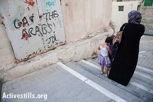 "A Palestinian woman and children pass the slogan ""Gas the Arabs! JDL"" spray-painted on an exterior wall of the Cordoba School near Shuhada Street, Hebron, October 22, 2012. ""JDL"" stands for Jewish Defense League, an extremist group founded by Meir Kahane and designated as a terrorist group by the FBI. On February 25, 1994, JDL charter member Baruch Goldstein opened fire on Muslims at Hebron's Al-Ibrahimi Mosque (Cave of the Patriarchs), killing 29 worshippers and injuring 125. Afterwards, the JDL designated him ""a martyr in Judaism's protracted struggle against Arab terrorism."" (photo by: Ryan Rodrick Beiler/Activestills.org)"