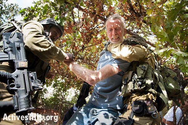 Israeli soldiers arrest an International Solidarity Movement volunteer for interfering in the attempted arrest of one of his colleagues who was filming confrontations between settlers, the Al Azzeh family which had just harvested their olives, and the military, October 22, 2012. (photo: Ryan Rodrick Beiler/Activestills.org)