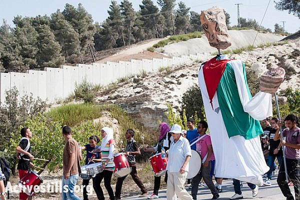 Carrying giant puppets, residents of Al-Walaja, together with Palestinian, international, and Israeli supporters, march through the West Bank village of Al-Walaja to protest the Israeli separation wall, September 28, 2012. If completed as planned, the wall will surround Al-Walaja and cut off its access to surrounding Palestinian communities. (photo: Ryan Rodrick Beiler/Activestills.org)