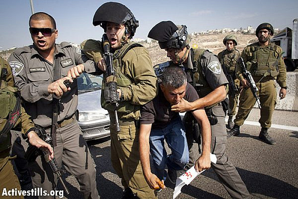 Israeli soldiers arrest Mohammad Khatib of the West Bank village of Bilin, as Palestinian and international activists block Road 443, October 16, 2012. (photo by: Oren Ziv/ Activestills.org)