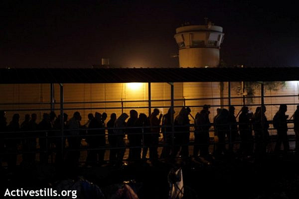Palestinians workers walk in the early morning next to the Wall and an Israeli military tower to cross the Eyal Israeli military checkpoint, November 2011 (photo: Activestills)