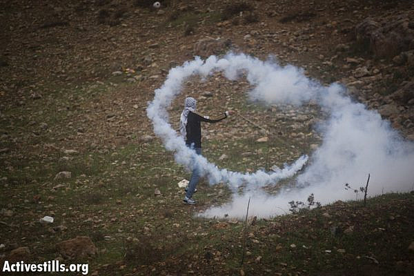 A Palestinian youth uses his sling shot to throw back a tear gas canister shot by the Israeli army during the weekly protest against the occupation in the West Bank village of Nabi Saleh, November 23, 2012. (Photo by: Oren Ziv/ Activestills.org)