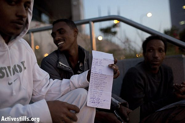 An African asylum seeker shows a list of names of some of those waiting to renew their temporary visa, outside the Israeli Ministry of Interior's offices in Tel Aviv, early morning, November 1, 2012. Asylum seekers gather from midnight outside the offices to be first in line. Only 60-70 visas are renewed each day, meaning many have to return the next day to repeat the process. Unlike Israelis coming to the offices, the asylum seekers are not allowed into the building. An officer comes out and takes the documents, leaving the applicants outside, sometimes waiting for hours. The 2A5 temporary visa must be renewed every 3 months, regardless of the amount of time a person has been living in Israel. The temporary visa is their only legal document issued by the Israeli government, and can be revoked at any time without reason. (photo by: Oren Ziv/ Activestills.org)